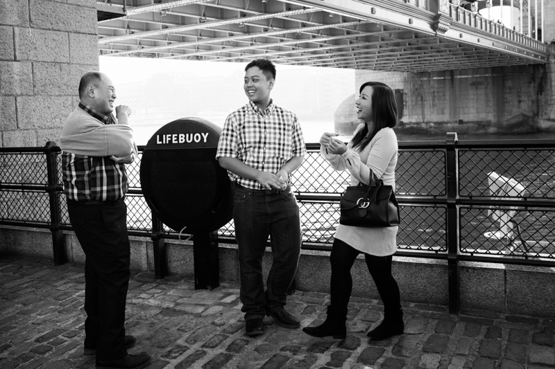 Husband, wife and son laughing next to Tower Bridge