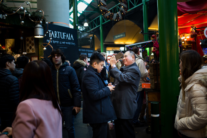Man taking a photograph in Borough Market