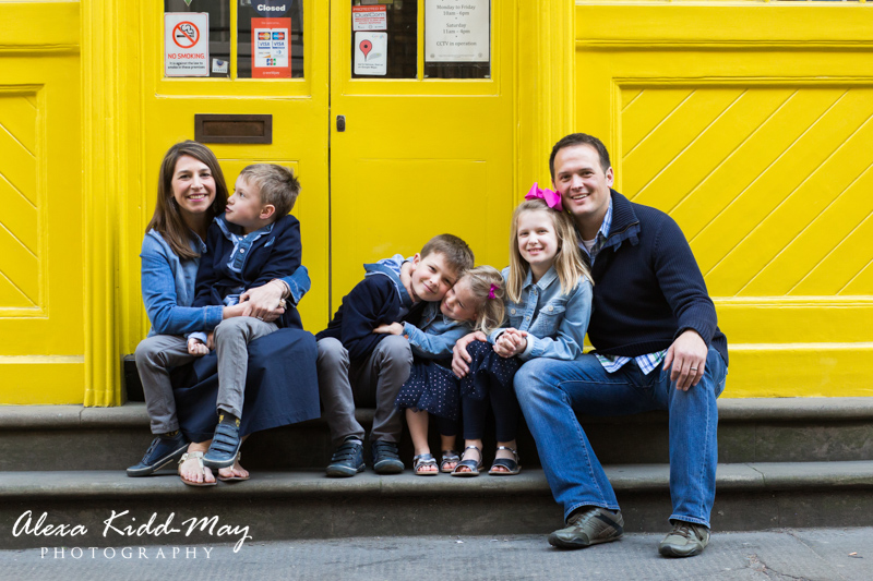 family sitting in front of yellow wall in Covent Garden London