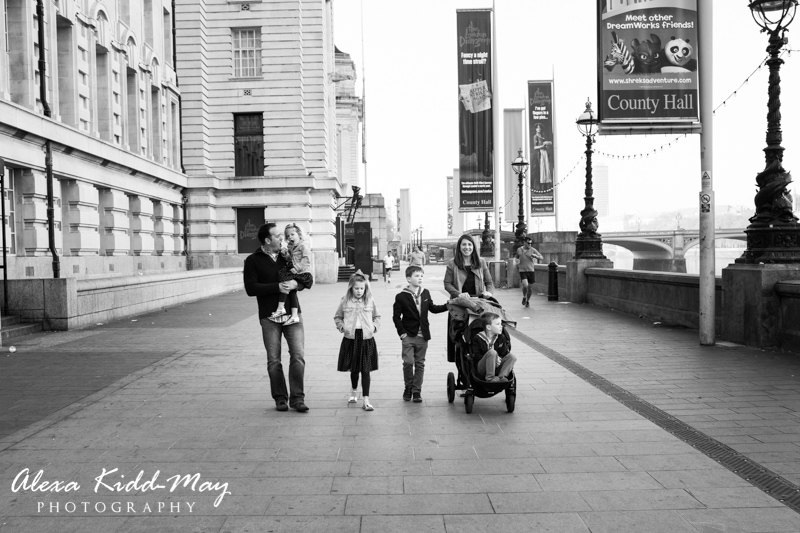 family walking by the river thames