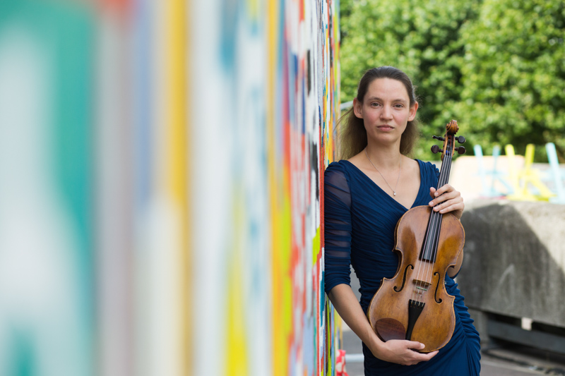 Lady and her viola leaning against a colourful painted wall at London's Southbank.