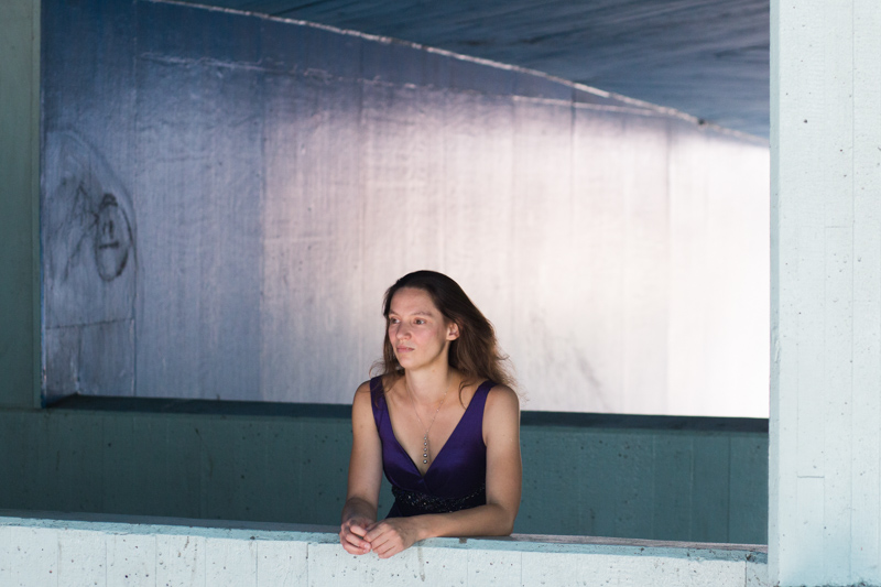 Lady leaning on a blue wall at London's Southbank.