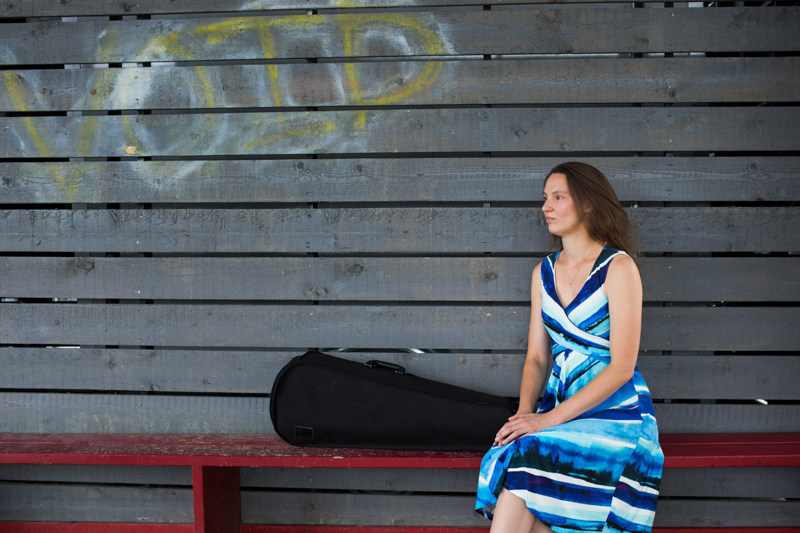 Lady sitting on a red bench with her viola case at London's Southbank.