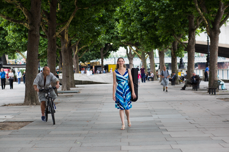 Lady walking with her viola case past some trees on London's Southbank.