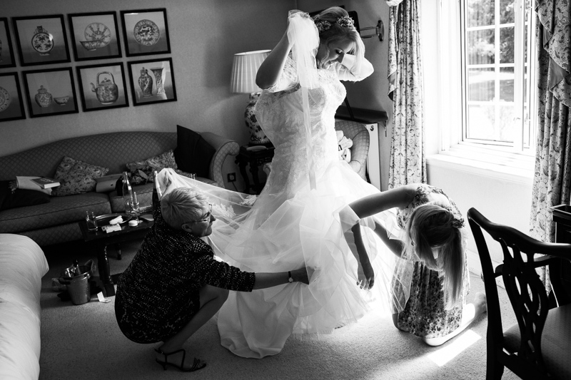 Bride putting her dress on, with help of mum and sister, at Bedford Arms Hotel