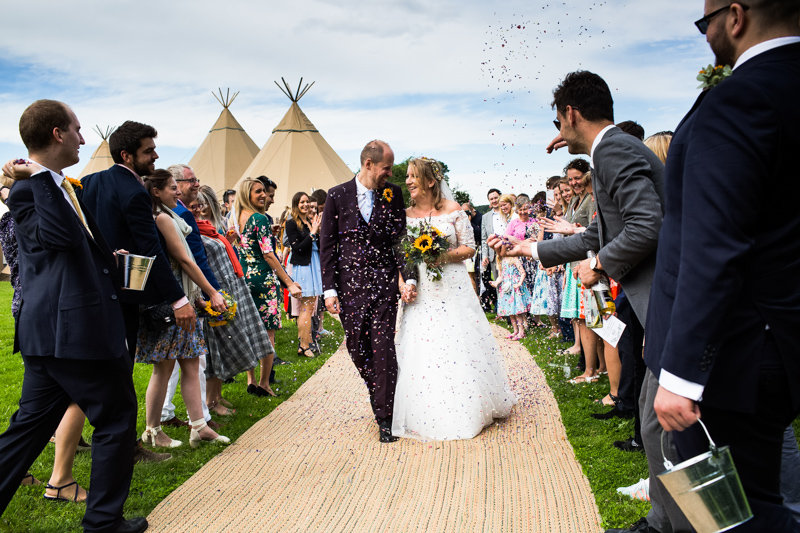 Bride and groom walking through the confetti in front of the tepees at their wedding at North Hill Farm, Chorleywood.