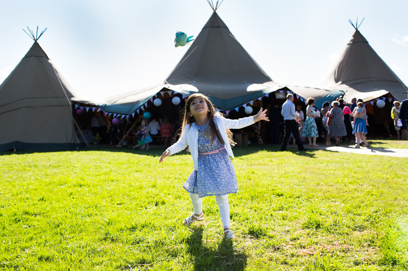 Girl throwing her toy in the air in front of the tepees at a wedding at North Hill Farm, Chorleywood.
