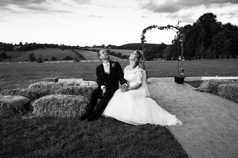 Bride and groom sitting on bales of hay, looking at the rain coming down at their wedding at North Hill Farm, Chorleywood.