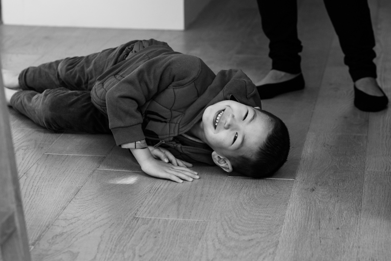 boy laughing on the floor in a half a Day in the Life photography session