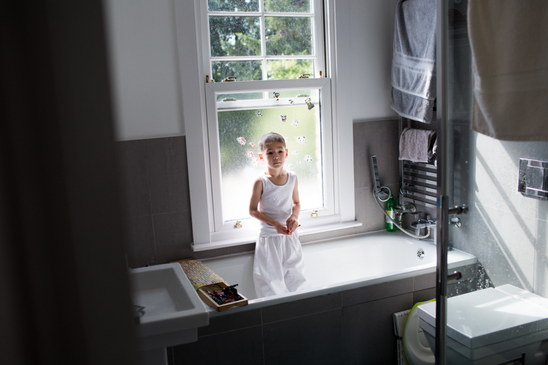 boy standing in his bath wearing his judo kit in a half a Day in the Life photography session