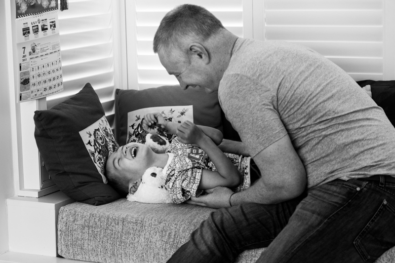father tickling son in a half a Day in the Life photography session