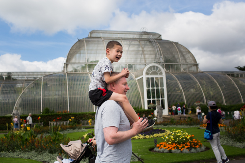 father doing a shoulder carry with his son in front of glass building in Kew Gardens in a half a Day in the Life photography session