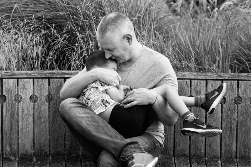 father cuddling his son on a bench in Kew Gardens in a half a Day in the Life photography session