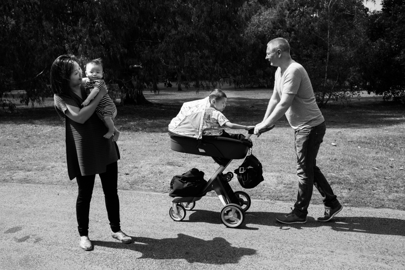 father pushing older son in a pram while mother hold baby in Kew Gardens in a half a Day in the Life photography session