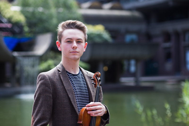 Formal portrait of a man and his violin at the Guildhall School of Music and Drama, Barbican