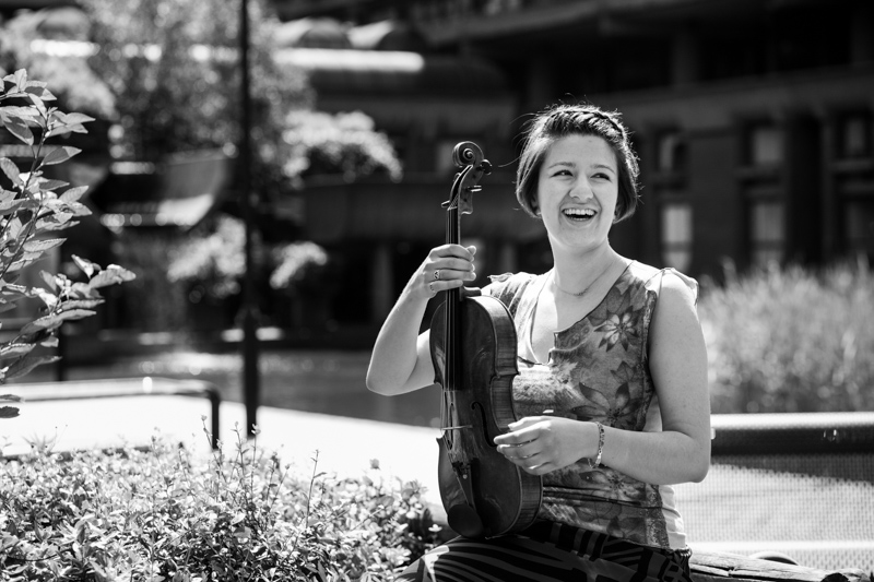 A lady holding her viola and laughing at the Guildhall School of Music and Drama, Barbican