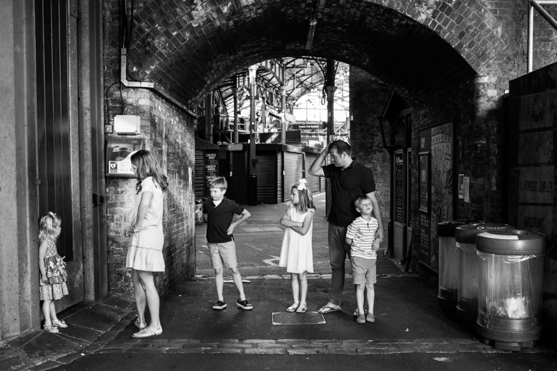 Family of six standing in an arch in Borough Market.