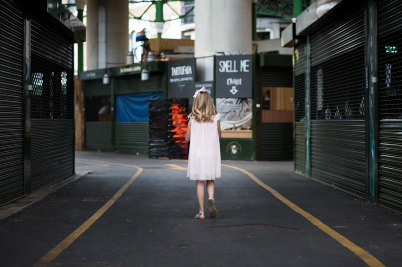 Girl in pink dress walking away from the camera in Borough Market.