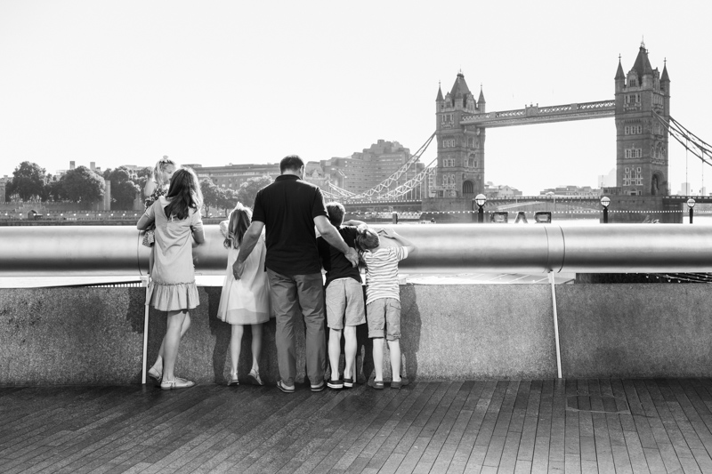 Family of six looking at Tower Bridge across the River Thames.