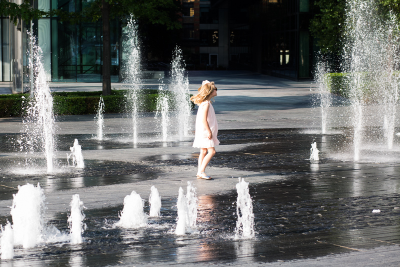 Girl in pink dress walking though fountains.