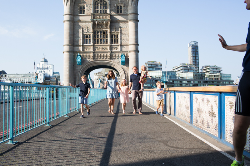 Family of six walking across Tower Bridge.