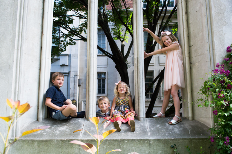 Four children in a big arched window.
