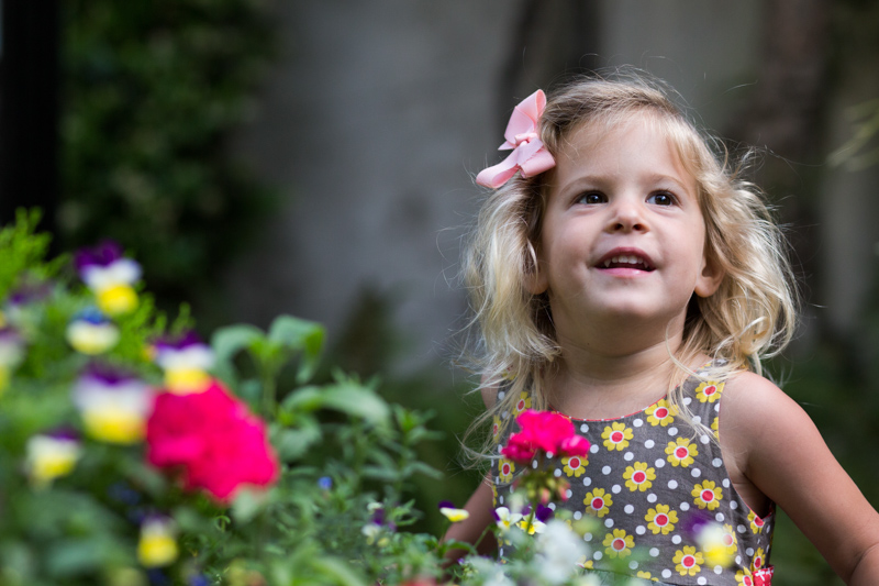 Girl with a pink bow in her hair behind some pink flowers.