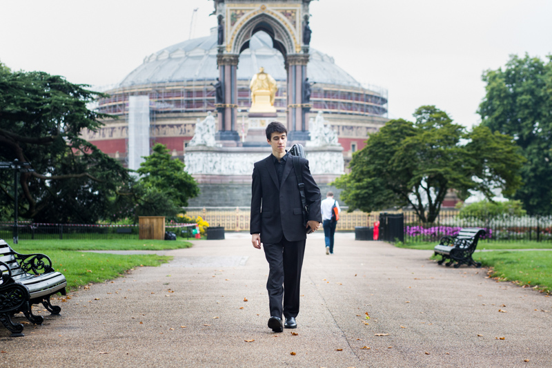 Man walking in front of the Royal Albert Hall and Albert Memorial.