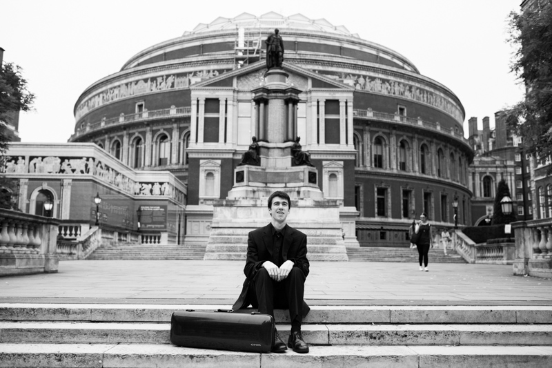 Man sitting on steps of Royal Albert Hall with his violin case.