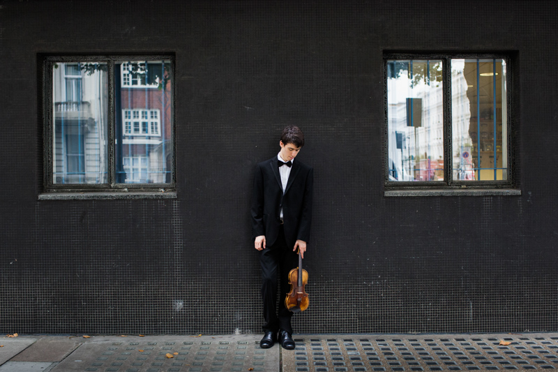 Man in DJ holding violin and looking down in front of black wall.