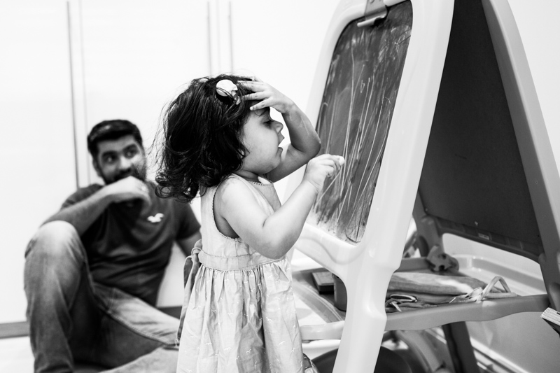 Girl with the hand on her head, drawing on a chalk board, with her Dad watching her.