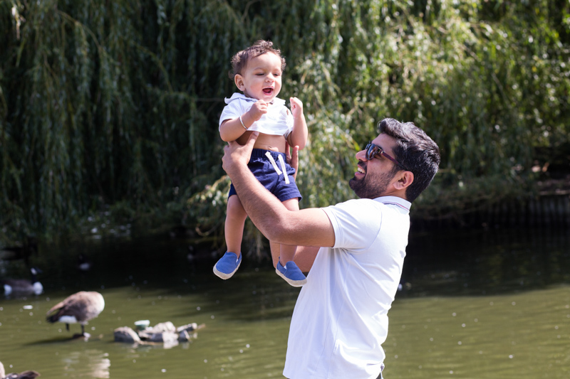Dad holding his baby boy in the air, with a duck pond behind them.