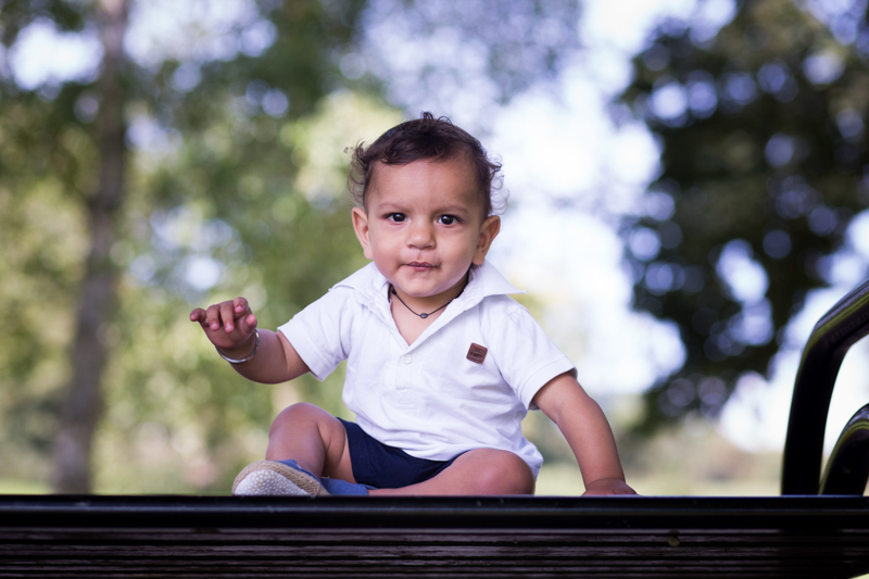 Portrait of a little baby boy on a bench.