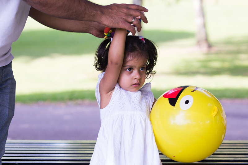 Dad's hands holding on to his daughter's hands, she's holding a yellow emoji ball.