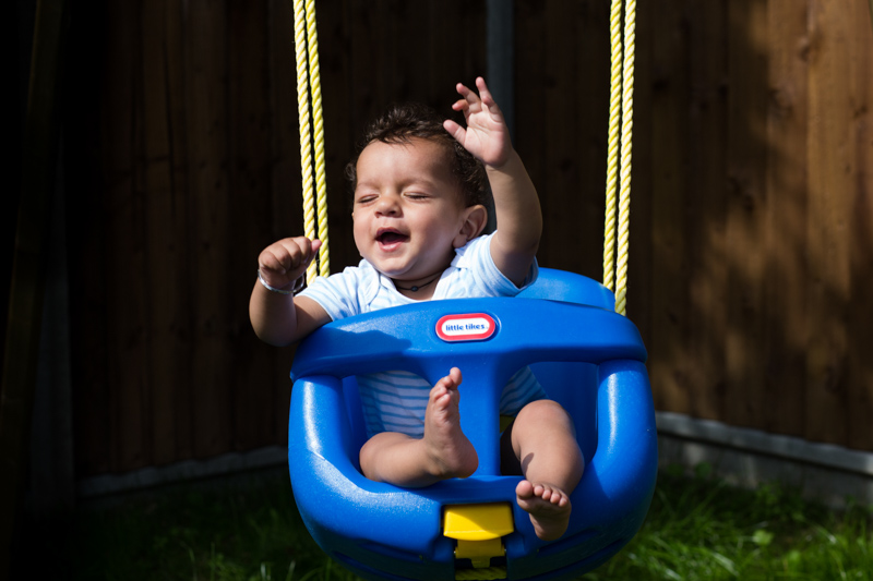 Baby boy enjoying himself on a swing.
