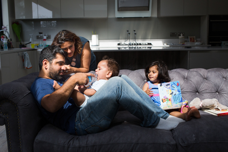 Family of four sitting on the sofa, the dad feeding water to his baby boy.