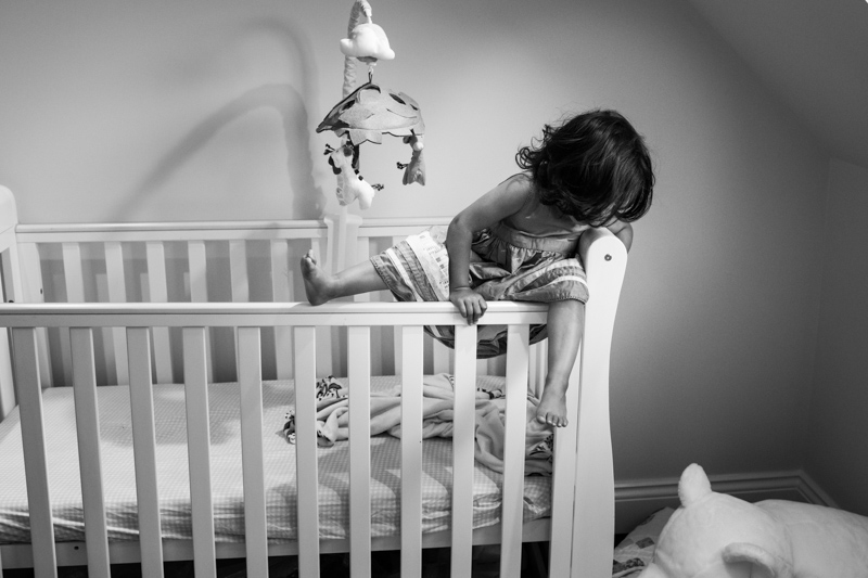 Little girl climbing out of cot.