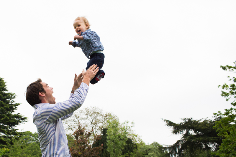 Man throwing his baby boy into the air.