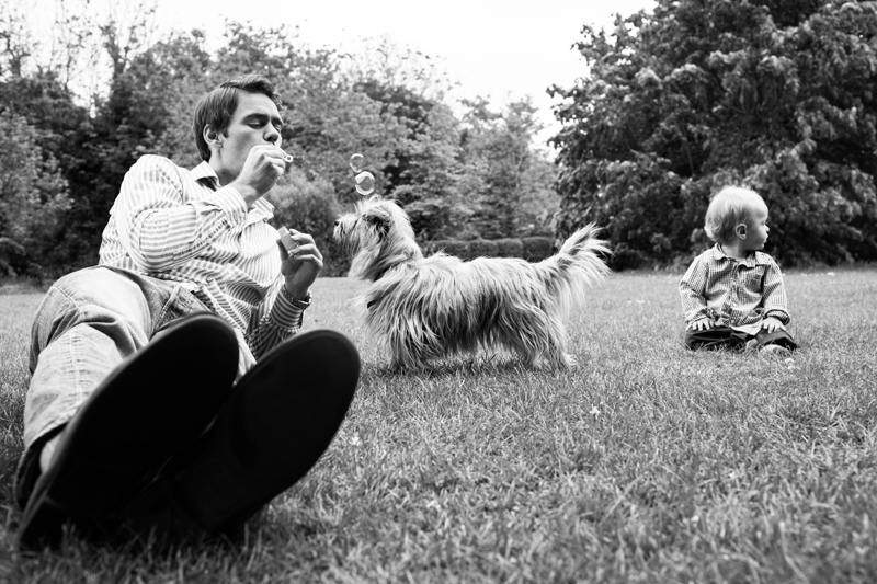 Dad blowing bubbles with dog and baby boy sitting next to him.