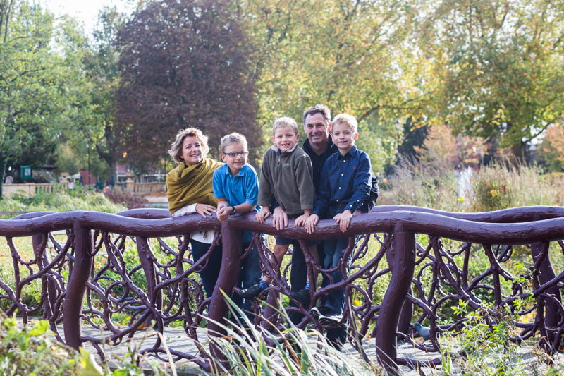 Family of five standing on a wooden bridge in the park.