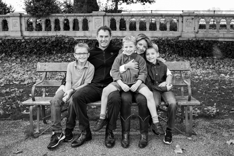 Family of five sitting on a bench in the park.