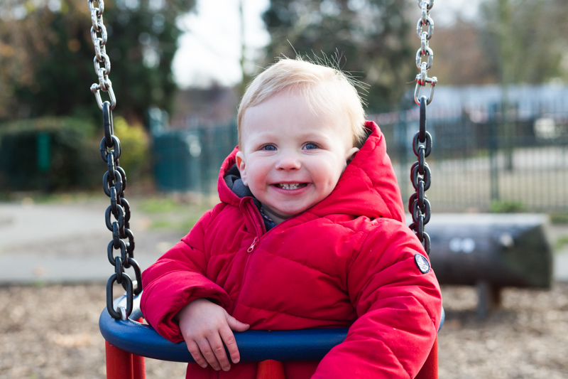 Baby boy in red coat on swing