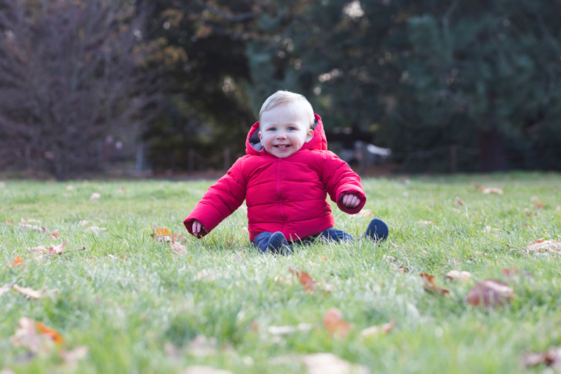 Baby boy in red jacket sitting on the grass smiling.