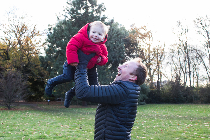 Dad holding his smiling baby boy in the air.