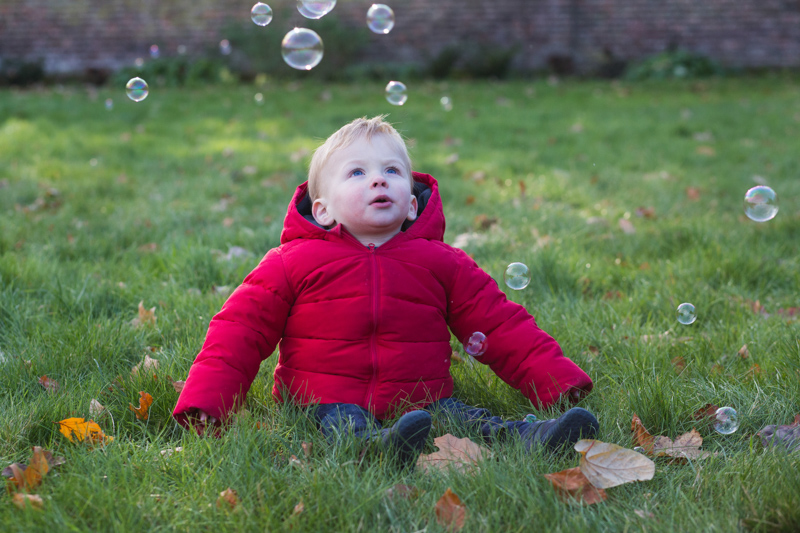 Baby boy in red jacket looking at bubbles.