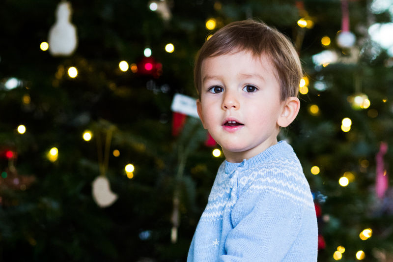 Boy smiling in front of Christmas tree.