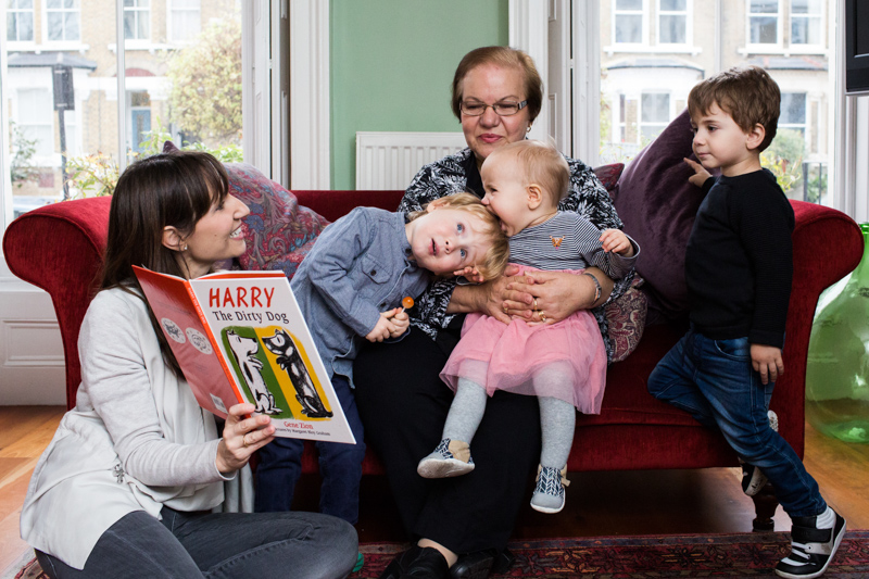 "Lady reading a book ""Harry the Dirty Dog"" to older lady, two boys and baby girl, who is biting one of the boy's heads."