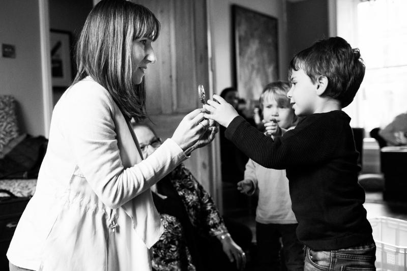 Mum handing little boy chocolate lollipop.