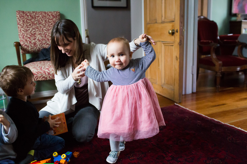 Lady holding hands of baby girl wearing pink tutu.