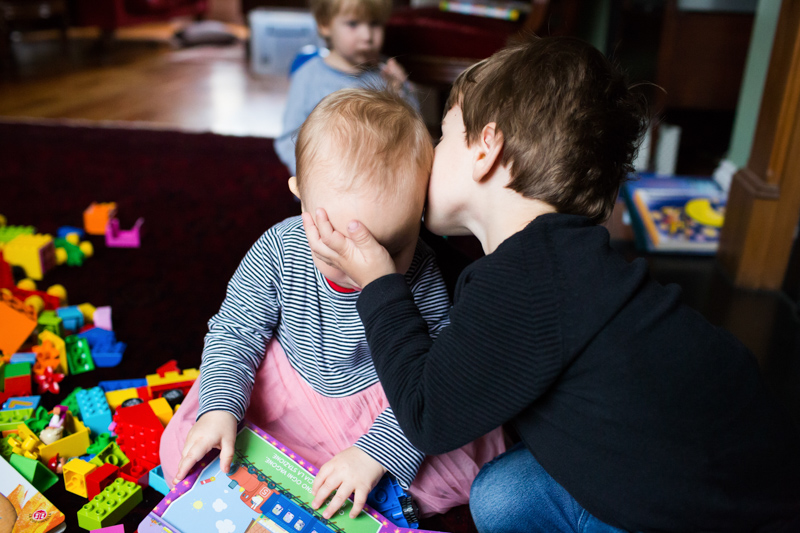 Boy kissing baby girl and holding her head.